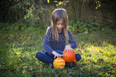 little girl sitting on meadow in