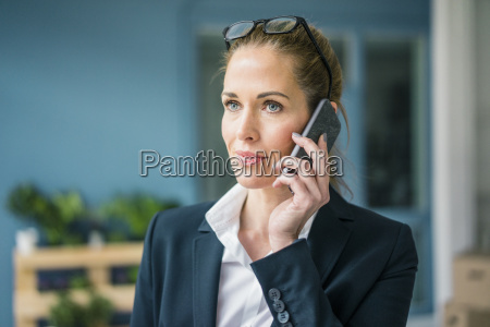 successful businesswoman standing at home talking