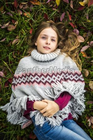portrait of girl wearing poncho lying