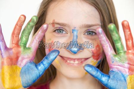 portraet des laechelnden maedchens mit fingerfarben
