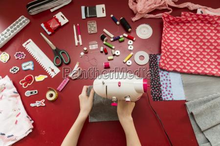 nahaufnahme von maedchen mit naehmaschine