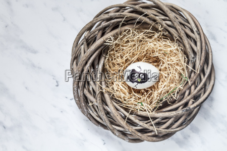 painted easter egg in nest with