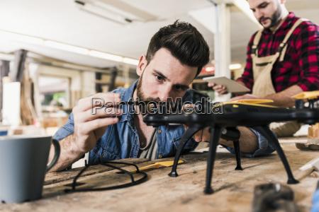 mann arbeitet in werkstatt an drohne