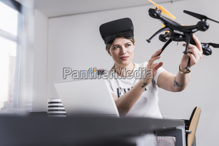 young woman with laptop and vr