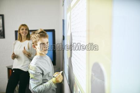 schueler im unterricht beim interaktiven whiteboard