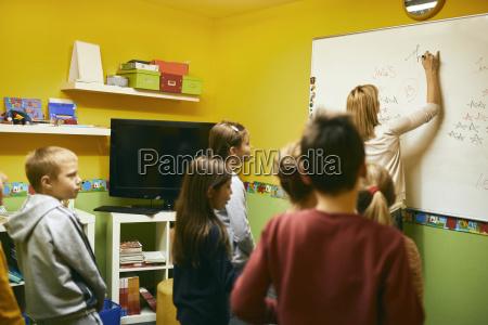 lehrer mit schuelern schreiben auf whiteboard