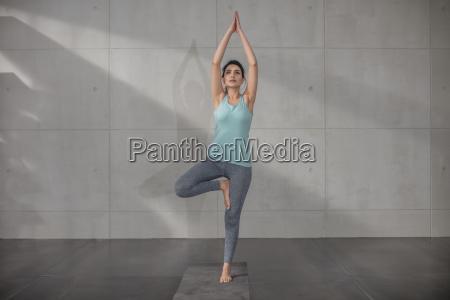 junge frau die yogauebung im studio