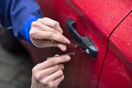 person die autotuer mit lockpicker oeffnet