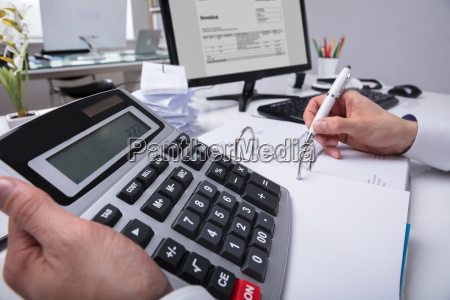 businesspersons hand calculating bill