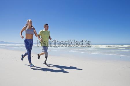man wearing prosthetic blade running along