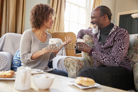 middle aged couple sitting around table