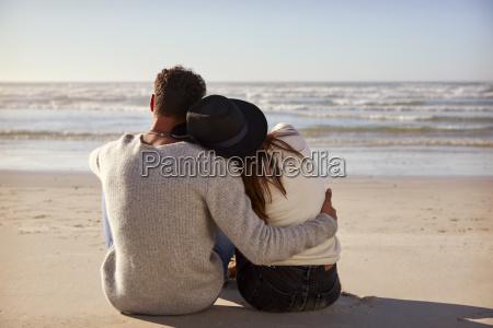 romantic couple sitting on winter beach