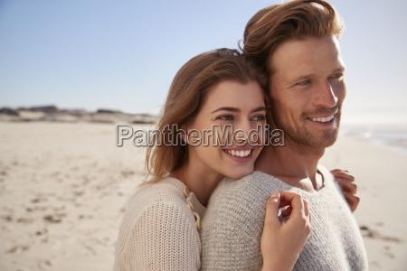 romantisches paar umarmt am winterstrand