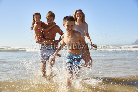 family on summer beach vacation run