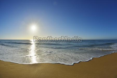 surf breaking on the shoreline of