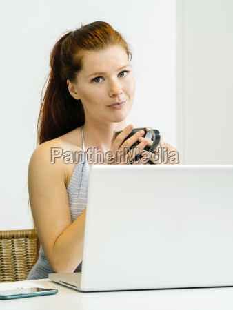 schoene rothaarige die laptop verwendet und