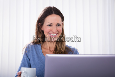 happy woman looking at laptop