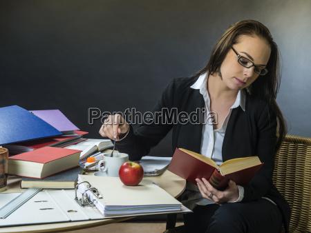 schoene lehrerin sitzt an ihrem schreibtisch