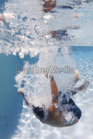 boy swimming underwater in pool