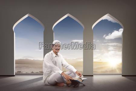 religioese asiatische muslimische mann mit koran