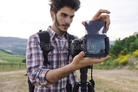 young male photographer inserting glass in
