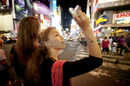 girl photographing through digital camera while