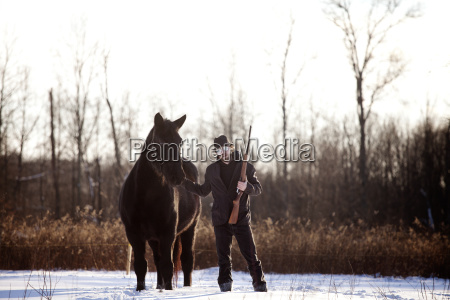 man holding rifle standing with horse