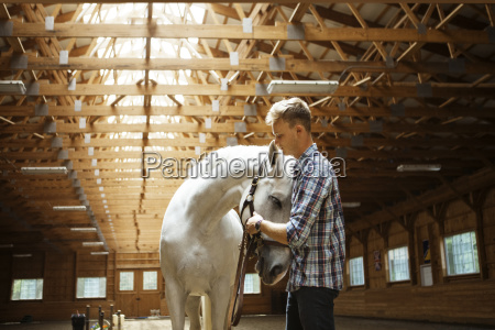 rancher stroking white horse in stable