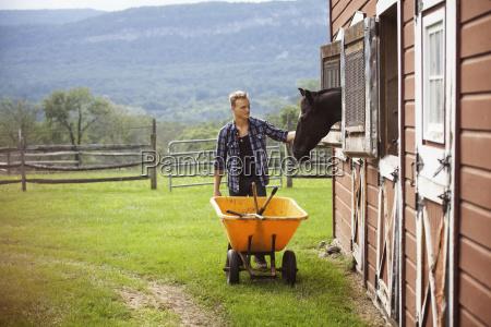 rancher stroking horse while pushing wheelbarrow