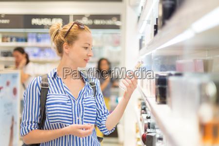 elegant blond young woman choosing perfume