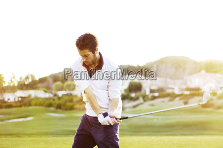 man holding golf club while standing