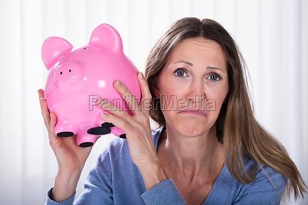 unhappy woman holding piggybank