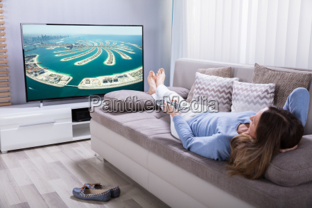 woman holding calculator while watching television