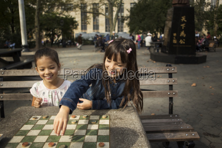 smiling sisters playing checkers game in