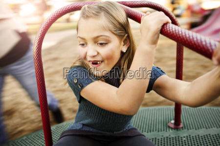 happy girl playing on merry go