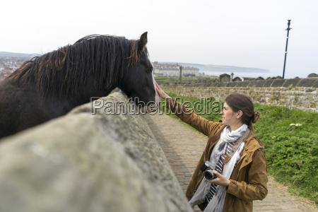 female tourist stroking horse peeking over