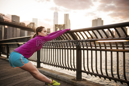 woman stretching at railing by river