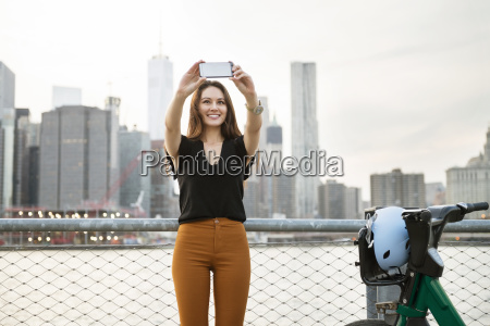 woman taking selfie while standing by