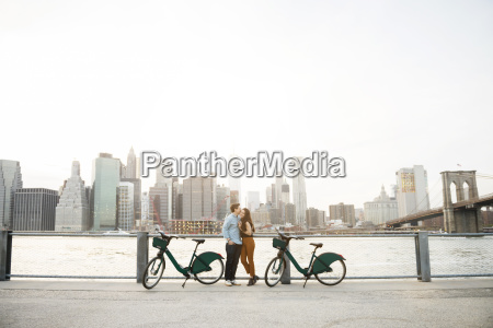 couple embracing while standing by bicycles