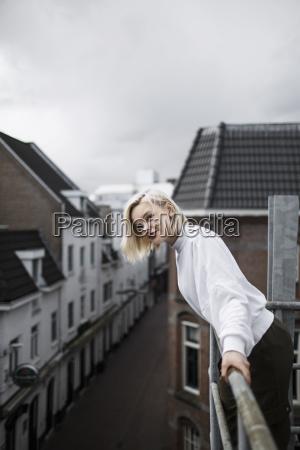 seitenansichtportraet der frau lehnend auf balkongelaender
