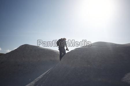 male backpacker walking on rock formation