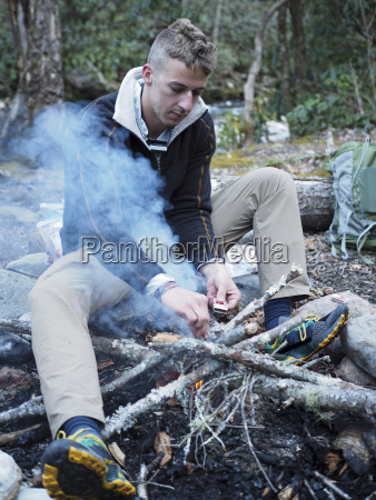 hiker lighting up campfire at pisgah