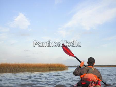 rear view of man kayaking on