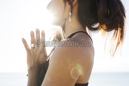mittelteil der frau meditierend auf strand