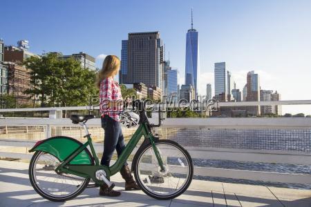 woman with bicycle walking on bridge