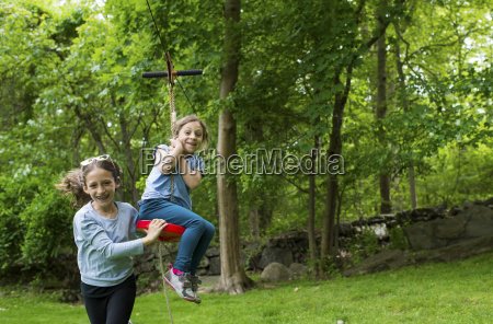 happy sisters playing with zip line