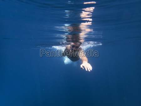 man swimming in sea underwater
