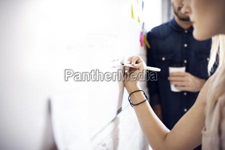 geschaeftsfrauschreiben auf whiteboard waehrend kollegeder im