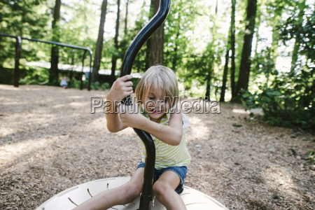 smiling girl playing on slide at