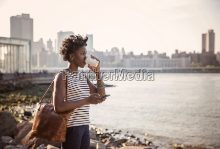 thoughtful woman drinking coffee while standing